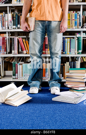 Student and books in library - Stock Photo