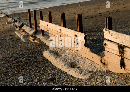 heavily eroded and storm damaged concrete groyne sea defences on Aberystwyth beach Wales UK in need of repair or - Stock Photo