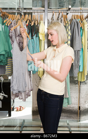 Woman shocked at clothes price - Stock Photo