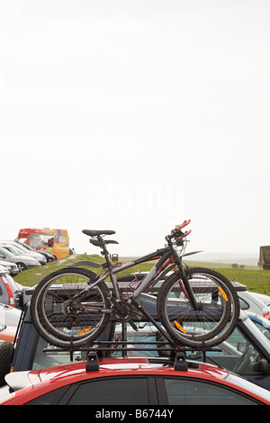Bicycles on car in car park - Stock Photo
