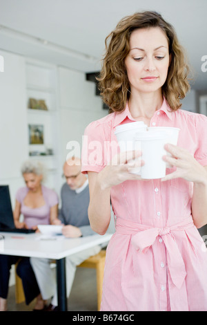 Woman carrying 3 cups - Stock Photo