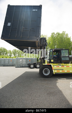 Forklift truck lifting cargo container - Stock Photo