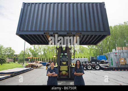 Colleagues by forklift truck - Stock Photo