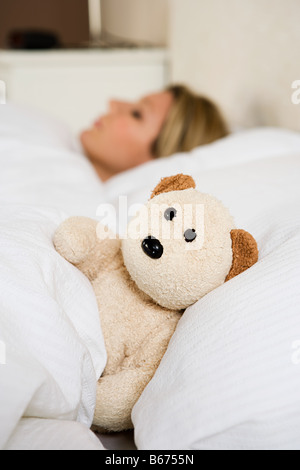 Woman in bed with teddy bear - Stock Photo
