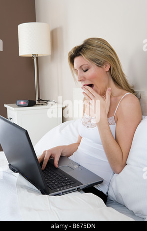 Woman in bed with laptop - Stock Photo