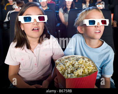 Boy and girl watching a 3d movie - Stock Photo