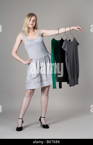 Woman hanging clothes on her arm - Stock Photo