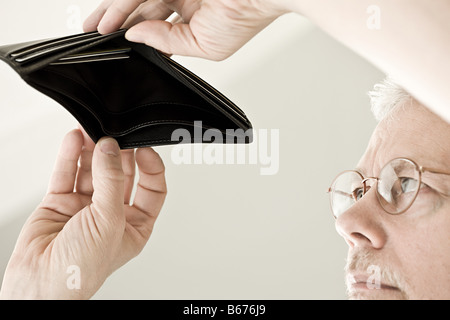 A man looking in an empty wallet - Stock Photo