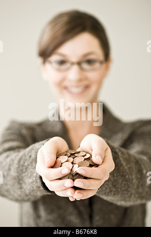 Young woman holding a pile of coins - Stock Photo