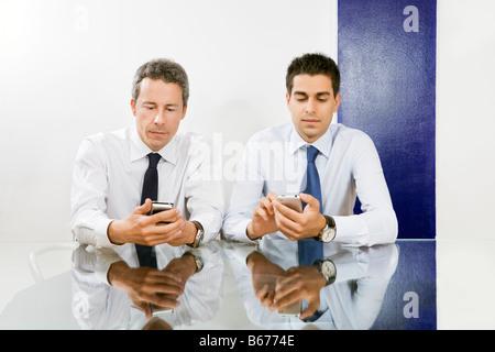 Two businessmen checking blackberries in meeting room - Stock Photo