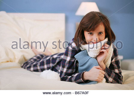 woman lying on a bed with hot water bottle in her arms - Stock Photo