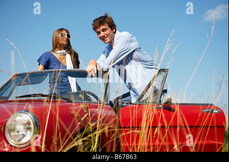 Couple in a red convertible - Stock Photo