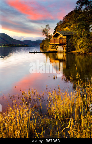 Dawn light illuminates the wooden boathouse on the shore of Ullswater near Pooley Bridge, Lake District, Cumbria, - Stock Photo