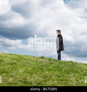 Lone man standing on hill - Stock Photo