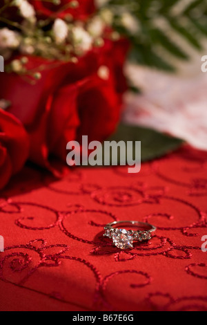Engagement ring on red box and roses - Stock Photo