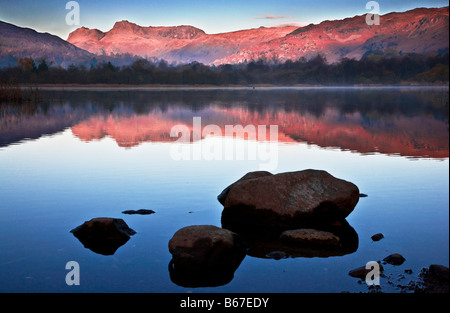 Dawn light illuminates the Langdale Pikes with a rosy glow reflected in the still waters of Elterwater Lake District England UK