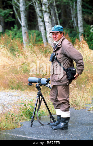 Birdwatcher bird watching with a Telescope in Pacific Rim National Park Reserve, Vancouver Island, BC, British Columbia, - Stock Photo