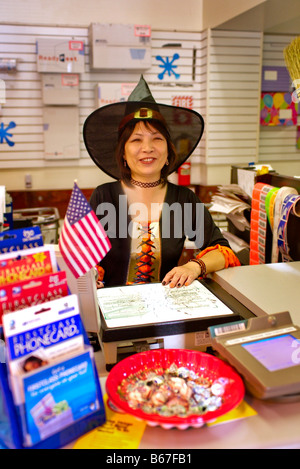 Asian-American US Postal Service clerk in witch costume day before Halloween in Laguna Niguel, CA - Stock Photo
