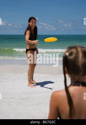 Mother and daughter (5-9) playing frisbee on beach - Stock Photo