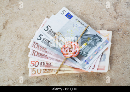 Close-up of European union currency tied with a ribbon - Stock Photo