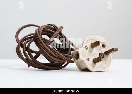 old white , UK standard 13 amp electrical plug and coil of brown flex - Stock Photo