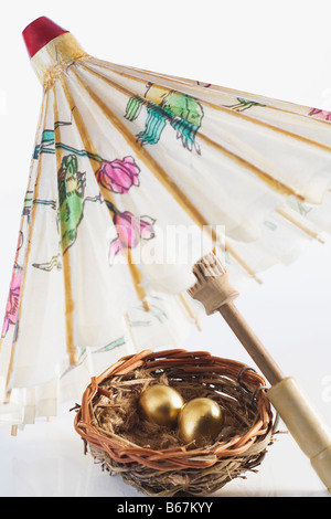 Close-up of golden eggs in a bird's nest with a parasol - Stock Photo