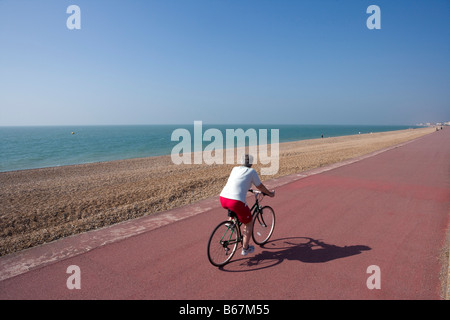 Cyclist on [coastal cycle route] at Hythe Kent [National Cycle Network route 2] - Stock Photo