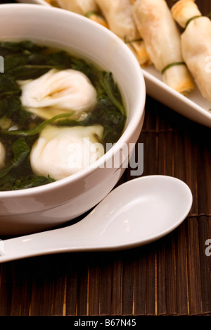 Close-up of Chinese dumplings in a bowl with sushi in the background - Stock Photo