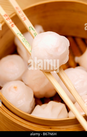 Close-up of Chinese dumplings being held in chopsticks - Stock Photo