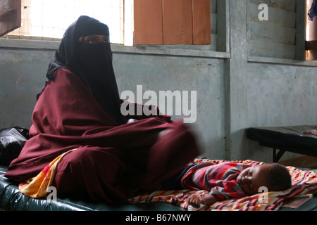 Undernourished somalian refugee boy with his mother in a hospital in refugee camp in Dadaab, at the border of Somalia - Stock Photo
