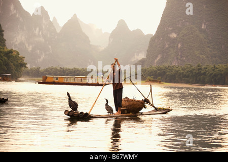 Fisherman on a wooden raft with a hill range in the background, Guilin Hills, XingPing, Yangshuo, Guangxi Province, - Stock Photo