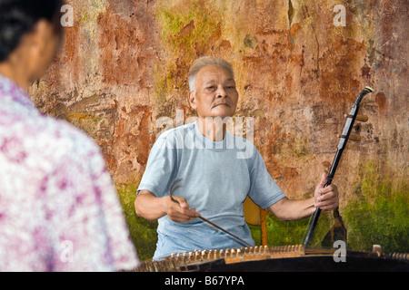 Senior man playing erhu, Fuli Village, Yangshuo, Guangxi Province, China - Stock Photo
