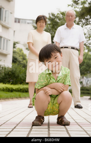 Portrait of a boy crouching and his grandparents standing behind him - Stock Photo