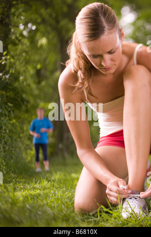 Female jogger tying lace, young man in Background - Stock Photo
