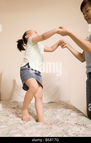 Mid adult woman playing with her daughter - Stock Photo