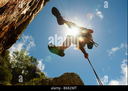 Man descending on abseil rope - Stock Photo