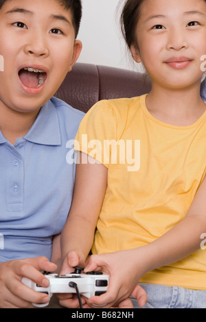 Close-up of a boy with his sister playing video game Stock Photo