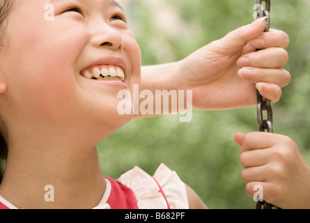 Close-up of a girl smiling on a swing - Stock Photo