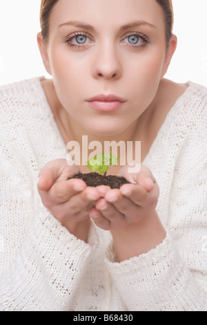 Woman Holding Plant in Soil - Stock Photo