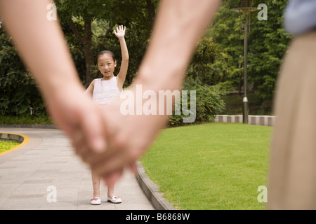 Girl standing in a garden and waving her hand to her parents - Stock Photo