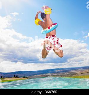 Man jumping in swimming pool - Stock Photo