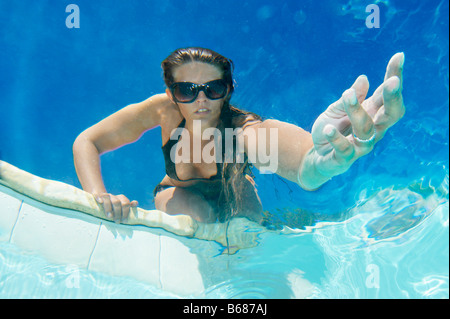 Woman holding out hand in pool - Stock Photo