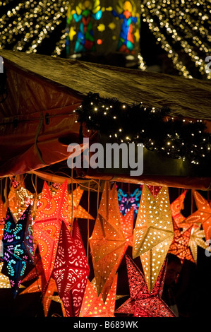 Light chains above stalls on a german christmas market - Stock Photo