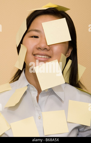 Portrait of a businesswoman covered with adhesive notes - Stock Photo