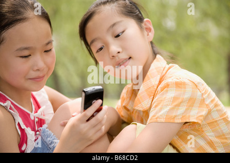 Two girls looking at a mobile phone - Stock Photo