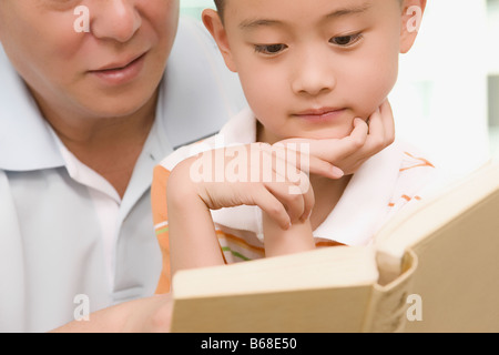 Boy reading a book with his grandfather - Stock Photo