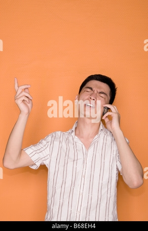 Male office worker talking on a mobile phone and looking shocked - Stock Photo