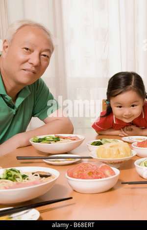 Portrait of a mature man sitting with his granddaughter at a dining table - Stock Photo