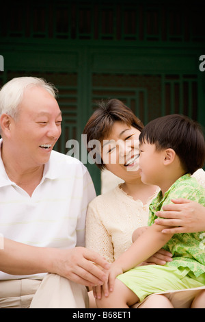 Side profile of a boy sitting with his grandparents and smiling - Stock Photo