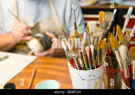 paint brushes in a decoy carvers studio - Stock Photo